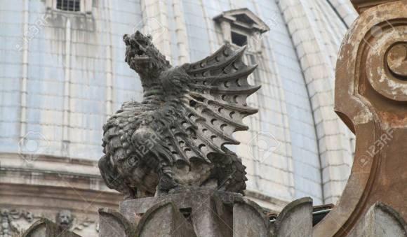 14249603-escultura-del-dragón-con-la-cúpula-de-la-basílica-de-san-pedro-en-el-fondo-la-ciudad-del-vaticano-europa