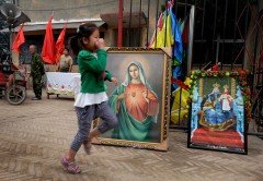 A child passes portraits of the Virgin Mary before the start of a religious parade at the Catholic cathedral in Donglu, Hebei Province on May 26, 2013. Police surrounded a Chinese village to prevent pilgrims from joining a Catholic parade to honour the Virgin Mary, who locals say appeared in the village a century ago. AFP PHOTO / Mark RALSTON
